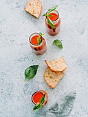From above of glass bottles with fresh cold gazpacho soup on rough gray surface with toasts and basil