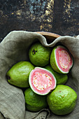 Guavas, whole and halved, on a linen cloth