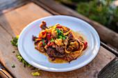 Portion geschmortes Schichtfleisch mit Bacon, Zwiebeln und Paprika