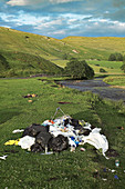 Fly tipping next to a river, Cumbria, UK