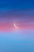 Waning crescent Moon and clouds at dawn