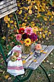 Herbstlicher Strauß aus Dahlien und Hagebutten auf Stuhl