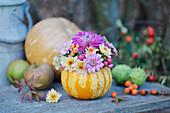 Kleiner Strauß aus Chrysanthemen in Kürbis als Vase