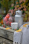 Old wine crate decorated for autumn with apples, milk churn and cup of tea