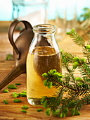 Homemade pine syrup in a glass bottle with a vintage funnel