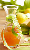 Homemade lemon syrup in a small carafe with a ribbon