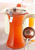 Summery homemade peach syrup in a preserving jar