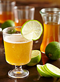 Mineral water with homemade caipirinha syrup as a refreshing drink with ginger, lime and sugar