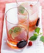 Raspberry syrup with ice cubes and lemon balm