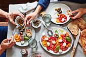 Paar isst Tomaten mit Mozzarella, Oliven und Kapern