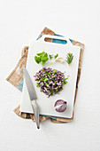 Chopped onions, herbs and garlic on a chopping board