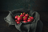 Radishes on a linen cloth in a bowl