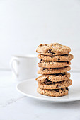 A stack of chocolate chip cookies with a cup of milk in the background