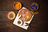 Various floral salts and dried flowers in bowls and on a wooden board