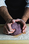 A man kneading a purple bread dough on a floured wooden surface
