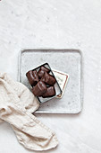 Chocolate candy with nuts and dates in gift box on white marble background