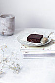 Vegan raw brownies with nuts and dates, on white marble background