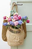 Frühlingsstrauß mit Hyazinthen, Tulpen, Narzissen und Ranunkeln in Korbtasche an Türe gehängt
