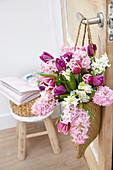 Frühlingsstrauß mit Hyazinthen und Tulpen in Tasche an Türe gehängt
