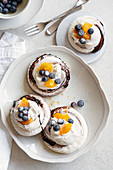 Mini pavlovas with marsala cream, orange and blueberries