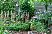 Buchsbaumgarten mit Rosen und Gartendekoration im Shabby Chic