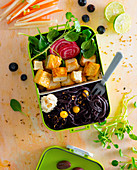 A bento box with tofu, black pasta, celery purée, spinach salad and beetroot