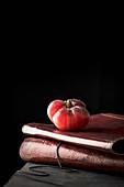 Reife rote Tomate auf alten Büchern