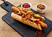 A hot dog with crispy onions, gherkins, mustard, mayonnaise and ketchup