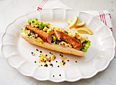 Viennese-style hot dog with potato salad and lemon wedges