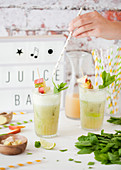 Adding a straw to a glass of pineapple fruit juice with mint, ginger and lime