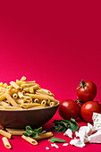 An arrangement of penne pasta, tomatoes, cheese and herbs