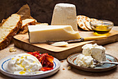 A cheese platter with olive oil and bread