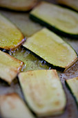 Courgette slices being roasted in oil