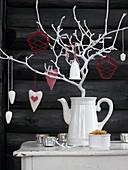 Weiß bemalter Zweig mit Anhängern in einer Kaffeekanne
