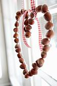 Heart-shaped garland of hazelnuts in window
