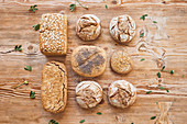 Composition of fresh hot tasty bread loaves, buns and baguettes on wooden table in bakery