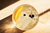 Glass of cool alcohol beverage with slice of fresh orange and small berries