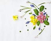 Künstlerische Gestaltung mit Narzissen-Blüten, Basilikum-Blättern, Ranunkelblüten und Traubenhyazinthen