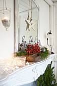 Weihnachtsdekoration mit Hagebutten, Kiefernzweigen, Kugeln, Sternen und Windlichtern