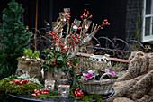 Winterliche Dekoration für die Terrasse mit Hagebutten, Zierkohl, Windlichtern, Knospenheide und Zieräpfeln
