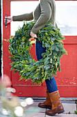 Frau trägt Kranz aus gemischten Koniferen-Zweigen mit Lichterkette