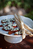 Getrocknete Tomaten, gefüllt mit Kräuterrisotto, dazu Grissini