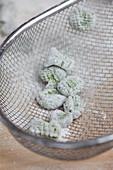 Green gnocchi in a sieve