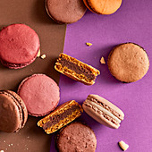 Assortment of colorful macarons on purple and brown background