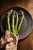Hand holding a bundle of fresh green asparagus in a paper bag