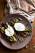 Grilled asparagus with mint leaves and a poached egg on toasted bread