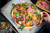 Pizza mit Tomatensalat und Trüffelsalami