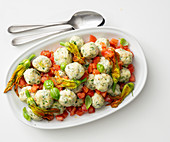 Ricotta and herb dumplings on a tomato medley with courgette flowers