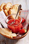 Homemade strawberry chutney in a preserving jar with bread, a napkin and a wooden bowl