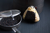 Onigiri, next to a pan for roasting sesame seeds (Japan)